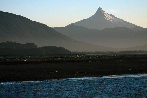 Sunset light across the Rio Yelcho - to the volcanic rock and glacial ice cap peak of Volcan Corcovado - a stratovolcano, rising to about 7,546 ft. (2,300 m), adjacent the Pacific Ocean.