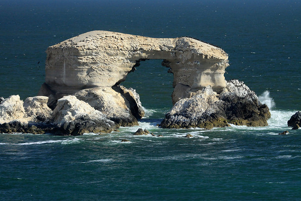 Wave breaking upon La Portada - this water-sculpted sea stack arch, measurres about 140 ft. (43 m) tall, 75 ft. (23 m) wide, and 230 ft. (70 m) long.