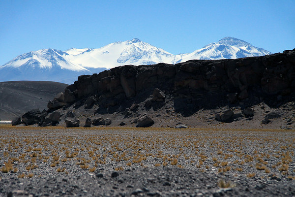 Across the rocky terrain of Paja Brava tussock grass - beyond the sunlit and shadowed lower northern slope of Cerro Pastillitos - to the distal peaks of Cerros Tres Cruces Norte (l), Central, and Sur (r), which forms the border with Argentina.