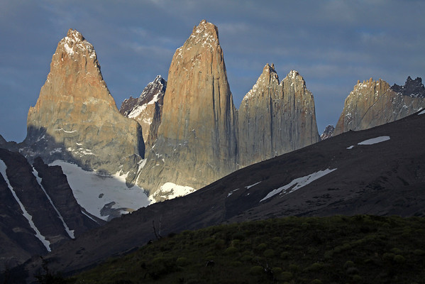 Early morning sunlight and shadows upon the Towers of Paine - Torre Sur (l), with the shadow of Mt. Almirante Nieto along its granite base, and adjacent to the glacier - beyond Sur's shaded northern buttress, to the metamorphic caprock of Cerro Fortaleza - Torre Central, and the adjacent Cerro Norte, with the sunlight now beginning to strike its twin peaks, but its lower face still cloud shaded - between the gap to the distal Cerro Escucio peak - Cerro Nido Condor (r), with the sun's direct rays beginning to beam upon the jagged granite peak, and lower cloud-shadowed hornfels ridge, of Cerro Nido Condor - foreground beyond the cushion plants, are the shaded slopes of Cerro Paine (r) and Mt. Almirante Nieto (l), displaying its glacial ice streams.