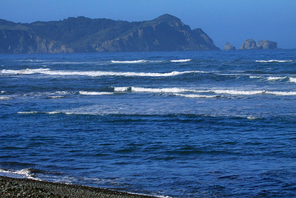 From the rocky shoreline - across the waves, upon the southern end of Bahia Cucao - to Punta Pirulil, and the sea stacks upon the Pacific - western Chiloé Island.