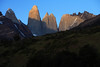 Beyond the lower vegetated slope of Cerro Paine, displaying southern beech trees and cushion plants - to the northern slope of Mt. Almirante Nieto (l) - and beyond to the early morning sunlight and shadows upon the Torres del Paine - with the distal sunlit summit of Cerro Fortaleza, between Torre Sur and Central - and Cerro Nido Condor, adjacent to the twin peaks of Cerro Norte.