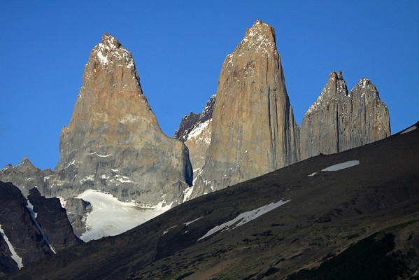 Beyond the slope of Cerro Paine (r) and lower slope of Mt. Almirante Nieto (l) - to the sunlit eastern faces of plutonic igneous granite, of Torre Sur, with the glacier below, and beyond it northern buttress to Cerro Fortaleza, displaying its metamorphic caprock - Torre Central, connected by the col Bich (gap or saddle), to Torre Norte, showing its twin peaks.