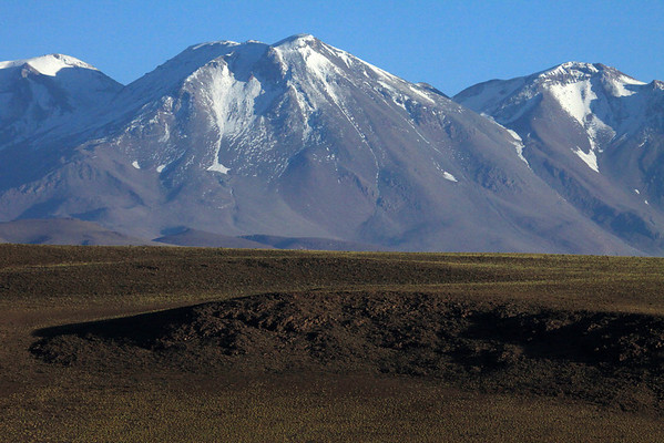 Beyond the slope of Cerro Carcote, scattered with xeric shrub and tussock grass - up to Volcan Aucanquilcha, its peak along the distal central ridge,