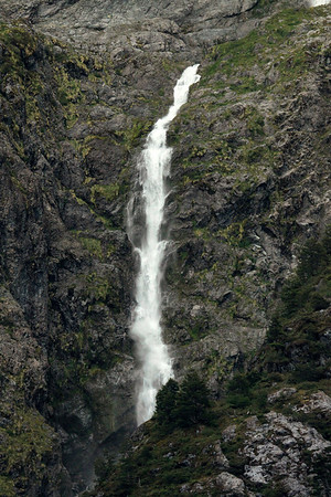 Beyond the southern beech trees, over the deep rocky ravine, to the steep igneous rock slope cloaked with Valdavian vegetation -  and the early summer season's glacial ice melt water, descending a ribbon falls - Aisen region, southern Chile, about 44°20'S and 72°30'W along the Patagonia Andes.