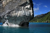 Capilla de Marmol - displaying its water eroded metamorphic marble base - across the glacial water, to the western shoreline of Lago Carrera.