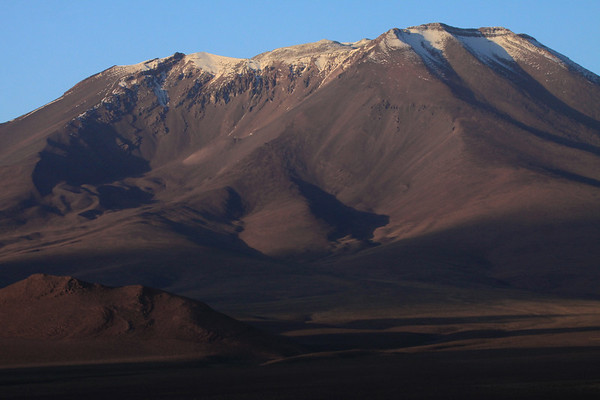 Early morning light, upon the snow-cloaked crater rim, of Cerro Palpana