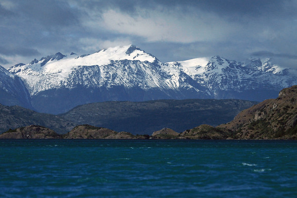 Southwestward across a rocky and vegetated island, upon Lago Carrera - over the partially cloud-shaded rocky and forested slope - to the glacial ice slopes of the Andes Mountains, amongst the clouds - early summer season - Aisen region.
