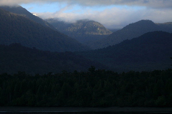 Early morning sunlight upon steep forested slopes of the Patagonia Andes - Aisen region.