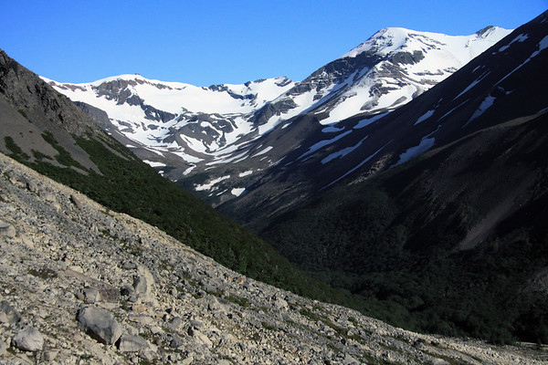 Down the glacial moraine - to the southern beech tree forest along the Valle Ascencio - between the lower sunlit slope of Cerro Nido Condor (l), and the mostly shaded slope of Cerro Paine (r) - and along the horizon the snow slopes at the northeastern end of Valle Silencio, to Cerro Koch.
