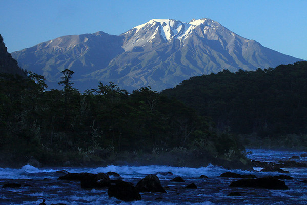 Down the shadowed glacial water rapids of the Rio Petrohue, among the igneous rock boulders, and surrounded by the Valdivian Temperate Forest ecoregion, the Vicente Rosales National Park - to the sunlit glacial ice cap, above the tree-line, upon Volcan Calbuco (northeastern view), the Llanquihue National Reserve - this is the Los Lagos region, the Patagonia Andes, southern Chile.