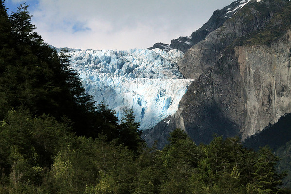 Across the Patagonia Andes vegetation of the Valdivian Temperate Rainforest ecoregion, to the sunlit seracs of the Ventisquero Colgante, part of the Queulat Ice Cap - adjacent the glacier carved intrusive igneous rock.