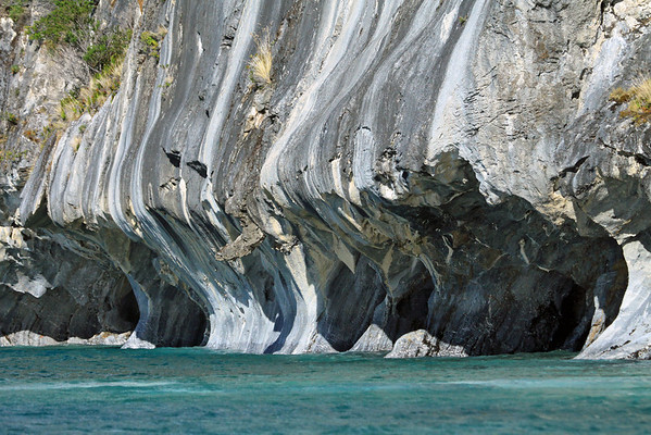 Across the glacial milk water of Lago Carrera - to the water eroded marble shoreline of Lago Carrera - displaying the opening to sea caves, arches, and a large protruding phallic-like overhang (below the large solo bunch of tussuck grass).