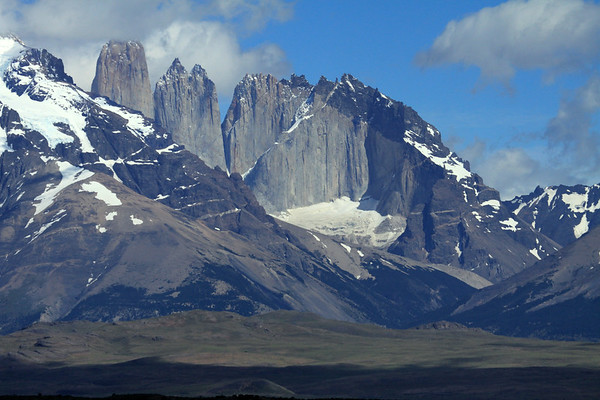 """Beyond the northern slope of Mount Almirante Nieto - and the cluster southern beech trees along the upper ridge of the Asencio Valley - to the distal Cerro Central (l), with its peak in the cloud) - the twin spire peak of Cerro Norte (c) - and Cerro Nido Condor (r) - Torres del Paine National Park - early summer season. """"Paine"""" (pie-nay), is from the indigenous Mapuche's language, meaning """"blue""""."""