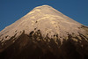 Morning sunlight upon the igneous rock slope and glacial ice cap peak, of Volcan Osorno - rising to about 8,730 ft. (2,661 m), along the Patagonia Andes.