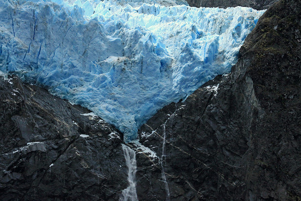 Sunlight peaking thru the clouds and onto the Ventisquero Colgante - displaying the seracs (a jagged pinnacle, column, or tower of ice located on the surface of a glacier, formed as a glacier flows down an icefall) - with its crests of both a plunge falls and cascade falls, descending the igneous rock below.