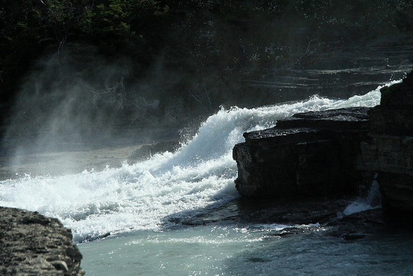 Mist from the chute falls, of the Cascada del Rio Paine - with the florescence of the daisies, blending in with the airborne water.