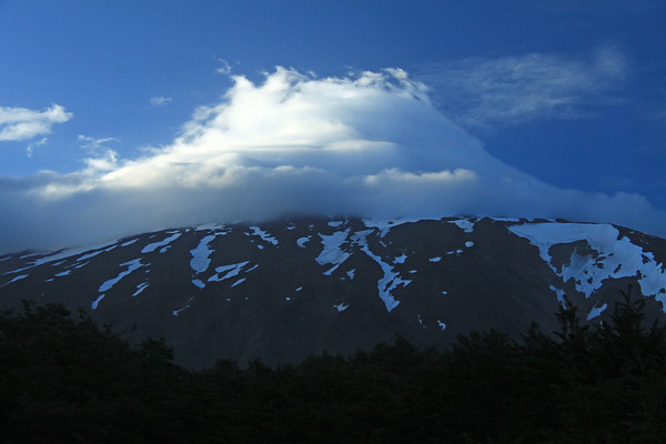 Early morning sunlight striking the cumulus cloud, engulfing the northern peak view of Volcan Lanin - the southeasternmost point of the Araucania region - central Chile.