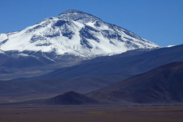 Beyond the cinder cone or scoria cone (a steep conical hill of volcanic debris) - up the western volcanic slope, to the peak of Cerro Tres Cruces Sur - the 2nd highest peak in Chile, rising to about 22,139 ft. (6,748 m) -and 5th highest in South America.