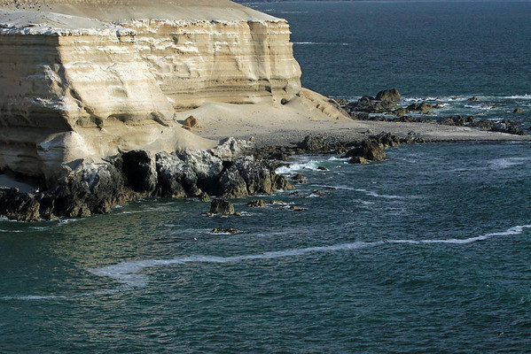 Afternoon sunlight along the coastline of Bahia Moreno - with the sandstone cliff above, and volcanic rock along the coastal Atacama Desert - Antofagasta region.
