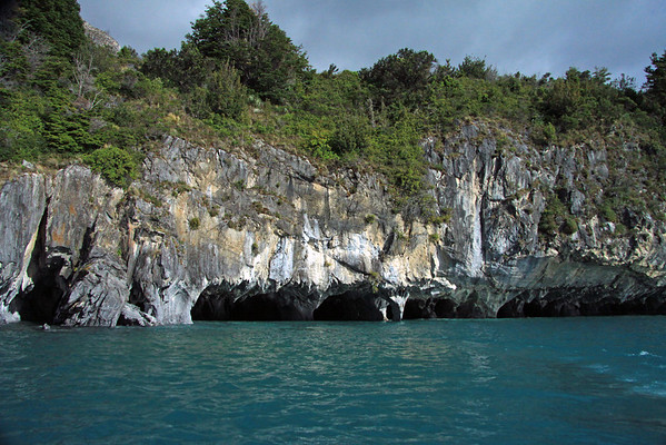 Metamorphic marble sea caves along the western shoreline of Lago Carrera - with the southern beech trees, tussock grass, and shrubs above - and the glacial milk or rock flour water below.