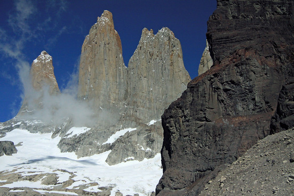 Beyond the lower slope of Cerro Nido Condor - to the snow-cloaked glacier, clouds, and Towers of Paine (Sur, mostly covered in clouds, Central, and the twin peaks of Norte) - with a slight glimpse, of the upper slope, of Cerro Nido Condor.
