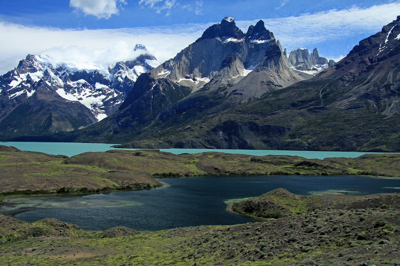 Across the Patagonia Steppe vegetation (composed of cushion plants, shrubs, and  grass) surrounding an endorheic lagoon - beyond the glacial milk/flour water of Lago Nordenskjold - to the Magellanic Forest ecoregion (southern beech trees), along the lower slope of Mt. Almirante Nieto (r) - Horns of Paine (c), with Mascara-Hoja-Espada distal - Cerro Paine Grande (l), Cumbre Principal, the highest point in the park at about 10,007 ft. (3,050 m), and the France Glacier.