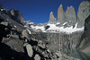 Beyond the mid-morning sunlight and shadows upon the boulders of plutonic rock till - and across the reflection upon the placid water of the glacial lagoon - to the snow-coated glacial ice, along the base of the Towers of Paine - with Cerro Nido Condor (r), the western slope of Mt. Almirante Nieto (l), and a slight glimpse of La Hoya (c).