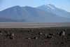 From the boulders and scrub vegetation - across the Solar Ascotan - beyond the lower southeastern slope of Cerro Puntilla - past Cerro Chijliapichina - to Volcan Ollagüe, rising to about 19,252 ft. (5,868 m) - Alto Loa National Reserve - northern Antofagasta region.