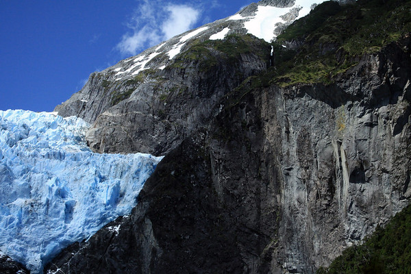 Sunlight and cloud shadows upon the glacial carved plutonic igneous rock slopes, of the Southern Volcanic Zone. of the southern Andes Mountains - the virgin vegetation of the Valdivian Temperate Rainforest - and the blue hue of the Ventisquero Colgante, part of the Queulat Ice Cap.