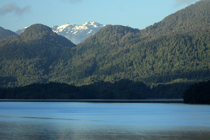 Across the waters of the fjord Glacier Sound (Seno Ventisquero) - beyond the predominately southern beech tree forest shoreline, of the Pacific Ocean - to the distal glacial slopes of the Patagonia Andes.