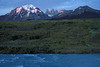 Across the glacial water rapids upon the Rio Paine - to the shadowed slope, scattered with cushion plants and shrubs - to the slope of Cerro Paine, with its lower slope cloaked with a Lenga Beech forest - to the day's first rays upon the Paine Massif (Cordillera Paine) - the glacial ice slope and peak of Mt. Almirante Nieto - to the sunlit peak of Torre Central and adjacent twin peaks of Torre Norte - with Cerro Nido Condor mostly illuminated - with the igneous granite Torre Sur (still shaded), but Cerro Fortaleza (distal) is revealing its sunlit upper ridge and peak of metamorphic rock.