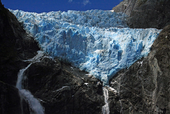 Sunlight and cloud shadows upon the crest of the twin plunge falls and a cascade/ribbon falls - and the blue hue of the terminus snout ice, with mineral silt there upon, of the Ventisquero Colgante.