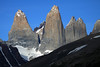 The sunlit, glacial sculpted, plutonic igneous granite spires of the Towers of Paine - Torre Sur, with with glacier below, and Cerro Fortaleza distal - Torre Central, attached to Torre Norte (twin peaks) - Cerro Nido Condor (r), and glimpse of Cerro Escucio - foreground is the mostly shadowed slope of Cerro Paine (r), and slope of Mt. Almirante Nieto (l), showing its glacial ice streams.