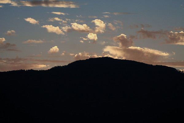 Sunset glow upon the cumulus clouds - with the forested ridge silhouette of Isla Puduguapi.