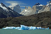 Glacial drift ice upon Lago Grey - over the rocky and vegetated peninsula - to the southern slope of Cerro Paine Grande (l) - Cuerno Norte, La Hoja, and La Espada (r) - and Cerro Fortaleza (distal, l), with a glimpse of Cerro Escudo (shield) beyond.