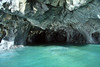 Beyond a marble sea column, into the sea cave - with the sunlit green hue, of the glacial water of Lago Carrera.