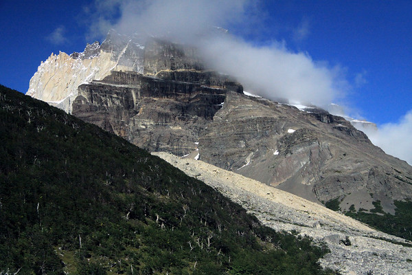 Beyond the southern beech tree forest, along the slope of Mt. Almirante Nieto - past the moraine rock debris, formed by glaciation - to Cerro Nido Condor, in the clouds - and a slight glimpse of Cerro Tridente.