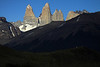 Beyond the cloud-shadowed lower slope of Cerro Paine - across the Asencio Valley, to the sunlit and shadowed glacial ice streams along the slope of Mt. Almirante Nieto, and distal peak of Punta Negra upon the horizon - to the sunlit granite and majestic Torres del Paine - Torre Sur, with the glacier below, and beyond its northern buttress to Cerro Fortaleza, revealing its metamorphic caprock - Torre Central, adjacent to the twin peaks of Torre Norte - and Cerro Nido Condor, displaying its jagged granite peak, and lower metamorphic hornfels slope.