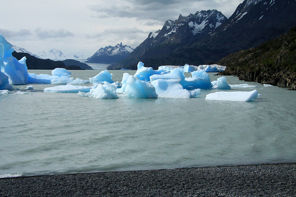 From the rocky southern shoreline of Lago Grey - northwestward along the rocky and vegetated peninsula shoreline, lined with bergy bits and icebergs - past the southern lower slopes of Cerro Paine Grande (r) - to Cerro Catedral, and the cirque glacier - next is the slope of Cerro Ostrava, which adjoins the Grey Glacier, which adjoins the Nanutak (outcrop) - then distal to Cerro Punzon and Cerro Piramides.