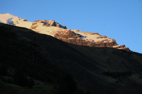Beyond the lower shaded slope, to the early morning light upon the upper northern ridge, of Cerro Almirante Nieto.
