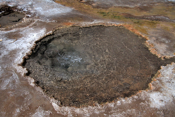 Geothermal hot spring discharging mineral rich water from around its circular formed silicious pool - Tatio Geyser Field - Loa province - northeastern Antofagasta region.