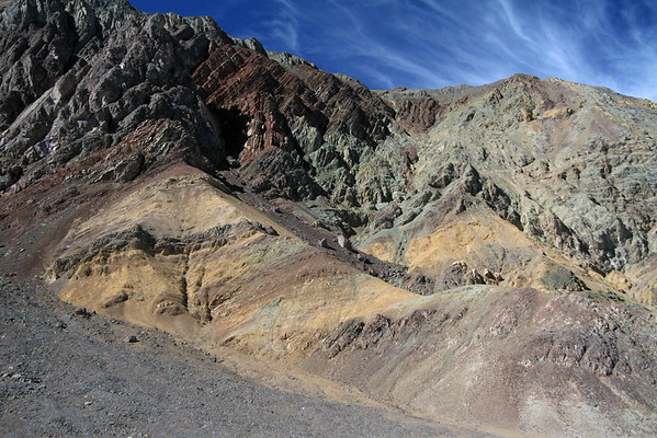 Colorful array of mineral pigments amongst the folded sedimentary rock slope - along the Quebrada Cortadera - with the cirrus clouds above - northeastern Copiapó province - Atacama region.