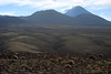 Mid-morning amongst the reddish tint spines upon the hemispheric clusters of Copana Cactus - beyond to the ridges along the southwestern slopes from below Volcán Sairecábur - and above to the cloud bank upon Volcán Licancabur, peaking at around 19,423 ft (5,920 m) - Loa province - Antofagasta province - also a portion of its crater rim forms the border at the southwesternmost point of the country of Bolivia, in the Potosi department.