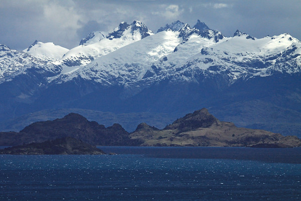 Western peninsula tip and mouth into the Vallecito village inlet - beyond to Isla Macías, displaying its twin peaks above the surface of the lake - with above the sunlight patches upon the snow-capped glaciers along the jagged ridges, upon the western slopes above Lago Bertrand - Aisén region.