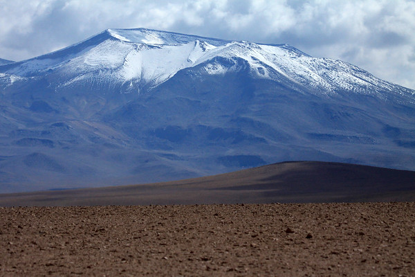 Volcán Tocorpuri, rising up to around 19,055 ft (5,808 m) and displaying its crater rim measuring about .8 mi (1.3 km) in diameter (western view) - Loa province - northeast Antofagasta region - with its S, E, and N rim marking the border with Bolivia (Potosi department).