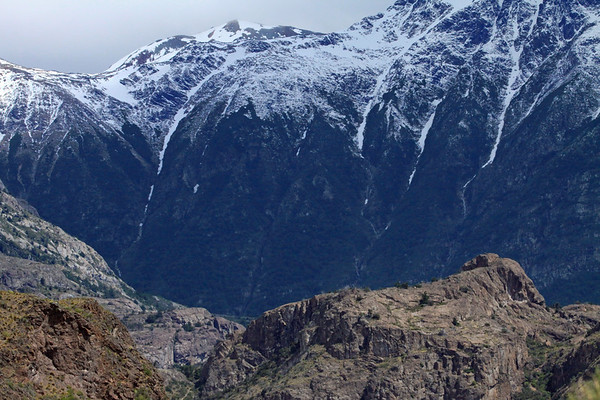 Lower and northern area of the Rio Laguna Bonita Valley, the steep slopes amongst the early-summer season snowbanks - with foreground the volcanic rock along the southern slope above Lake General Carrera - Aisén region.