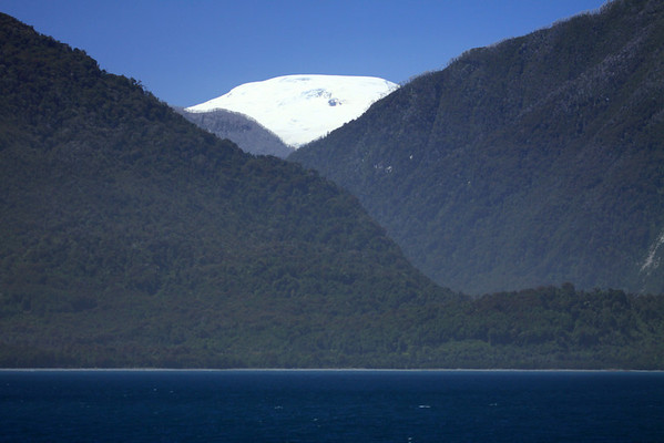 Gulf of Corcovado - across the forested slope of Puduguapi Island, along the peninsula to Punta Becerra - and above the snow-capped glacier - Palena province - Los Lagos region.