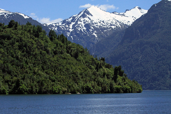 Mouth of the Puerto Chacabuco Bay - at the headland slope and eastern end of the Chacabuco Peninsula - and beyond to the the forested slopes, igneous rock ridges, and waterfalls along the head of the Aisén Fjord and the Pacific Ocean - Aisén province and region.