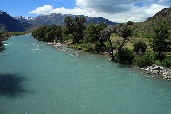 Rocky shoreline, southen beech trees, and glacial/snowmelt water along the Rio Laguna Bonita, here near its northern mouth into Lake General Carrera at the angled headland slope - with above the early-summer season snow banks upon the slopes and ridges along the Sierra Avallanos, near the mouth of the Rio Avallanos into the lake - Aisén region.